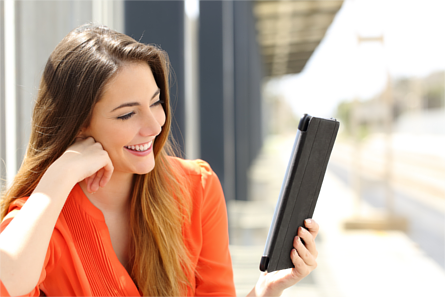 Woman smiling while reading a tablet device