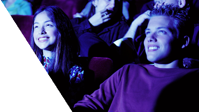 Young girl and boy watching a movie in the cinema