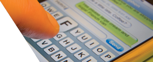 A closeup image of a person typing a text message on an iPhone