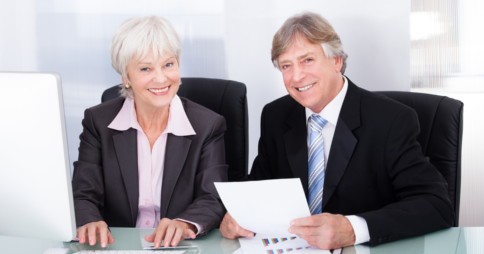 Elderly woman and man in office attire