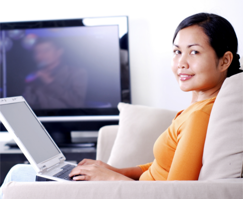 Woman seated on a couch using a laptop, with TV on in the background
