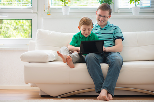 Father and son sitting on a sofa using a laptop together