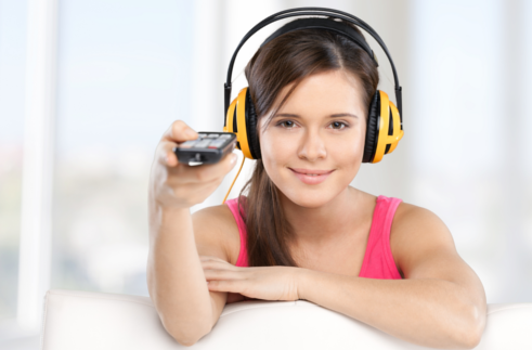 Girl wearing headphones, pointing a remote control with her right hand