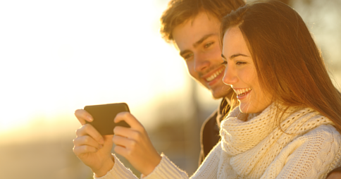 Man and woman smiling while viewing media on a smartphone together