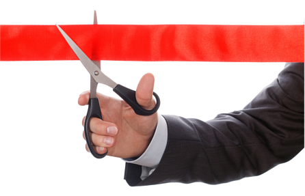 Businessman holding an open pair of scissors up to a line of red tape