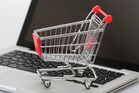 Miniature shopping cart resting on a laptop keyboard. Image credit:  Tim Reckmann, Flickr