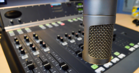 Microphone in front of an audio mixing console. Image credit: marvinjvds via Flickr