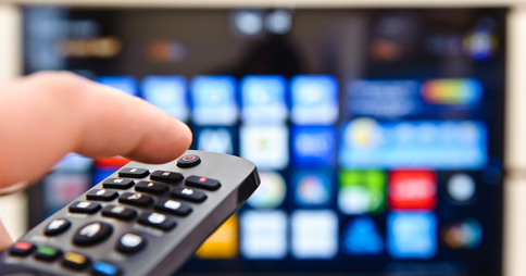 Left hand pointing a remote control at a Smart TV