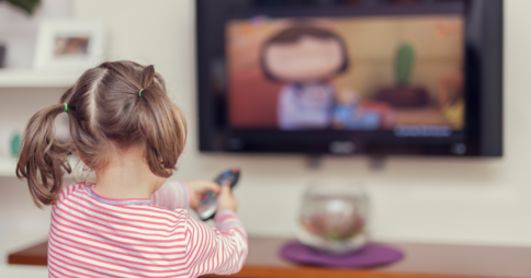 Little girl pointing remote control at a cartoon on TV