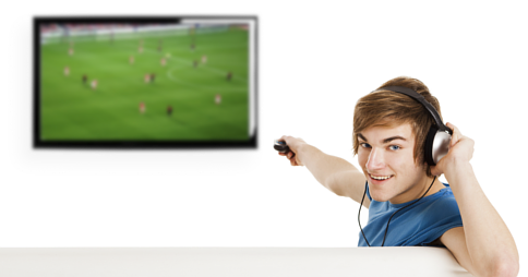 Man wearing headphones while pointing remote control at TV