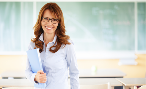Smiling teacher standing in a classroom, holding a folder in her right hand