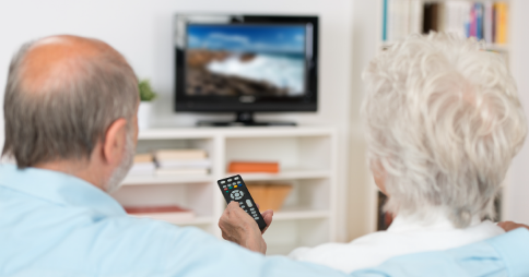 Elderly couple watching TV together. Woman pointing remote at screen. Image credit: Defining progress for Access Services on Video on Demand (VOD)