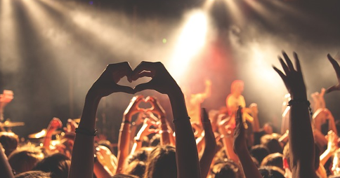 Audience cheering whilst facing the stage at a live performance. A person's hands are raised in the foreground making a 'heart' shape.