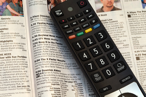Remote control resting on a TV guide