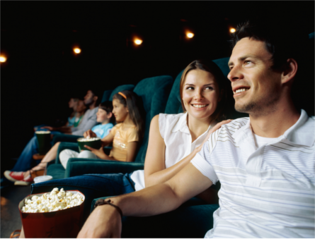 People seated in a movie theatre, facing the screen. Couple in foreground with box of popcorn resting in-between them