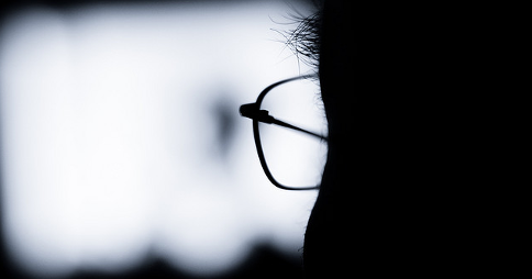 Silhouette of a man with glasses watching TV. Image credit: XiXiDu via Flickr