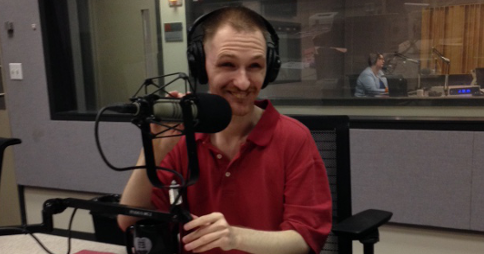 Robert Kingett in the WEBZ studio, wearing headphones and sitting behind a microphone