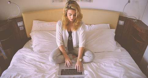 Woman sitting on a bed, using a laptop