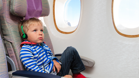 Little boy wearing headphones inflight