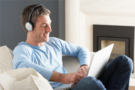 Man on sitting on a couch, smiling whilst wearing headphones connected to a laptop