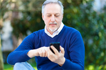 Mature man using a smartphone outdoors