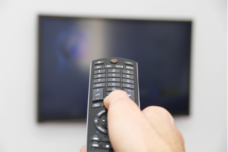 Right hand pointing a remote control towards a TV screen