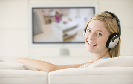 Woman smiles as she wears headphones while watching TV