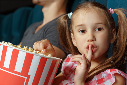 "Little girl holding popcorn in a cinema, making a ""shh"" gesture"