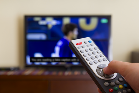 Right hand holding remote control in front of captioned sporting event on television