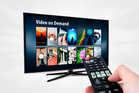 Left hand pointing a remote control at a Smart TV displaying a Video on Demand app
