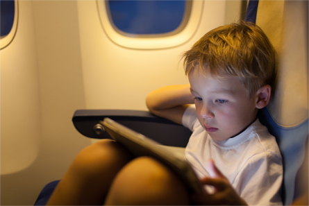 Young boy watching a tablet device in-flight