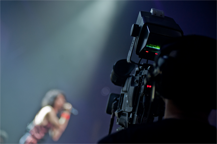 Cameraman recording a singer live on stage