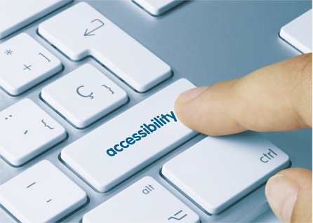 Finger resting on an accessibility button on a computer keyboard