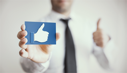 Man giving thumbs up whilst holding card with Facebook 'like' icon
