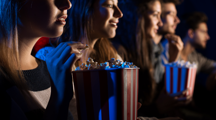 People eating popcorn in a movie theatre