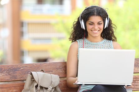 Woman using a laptop with headphones outdoors