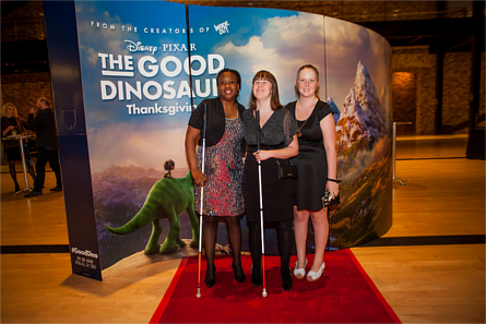 Attendees of Pixar's 'White Canes, Red Carpet' event standing in front of a poster for 'The Good Dinosaur'. Image credit: Guide Dogs for the Blind, Flickr