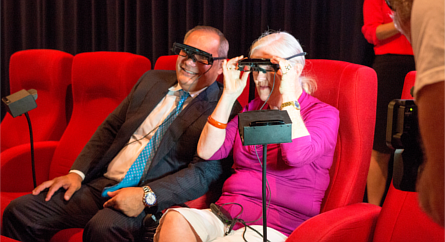 Mayor Tom Tate and Kerry Campbell using captioning glasses to watch a movie.