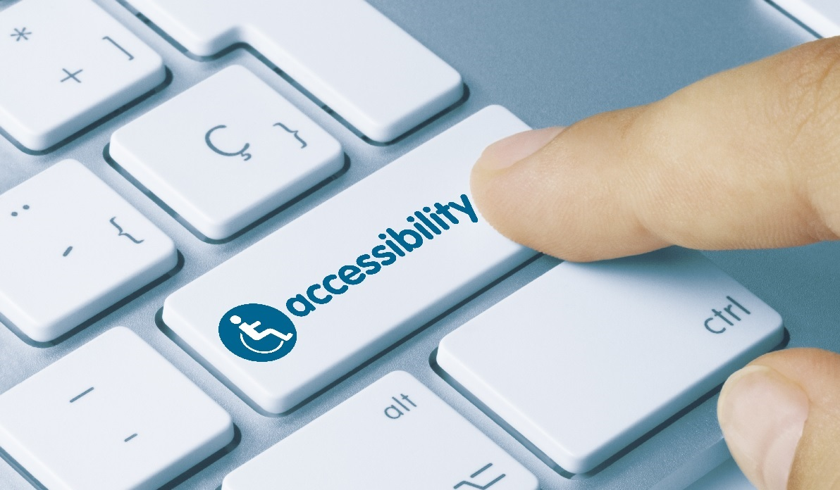 A finger presses an Accessibility key on a laptop