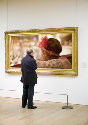 A man looking at a painting in an art gallery.