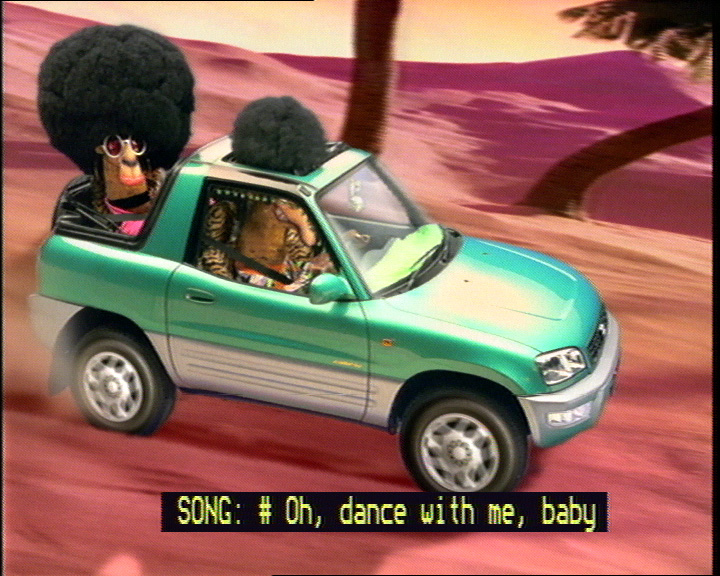 Example of captioned lyrics: frame from movie showing animated camels with afros singing in a car with captions: 'SONG: #Oh, dance with me, baby'