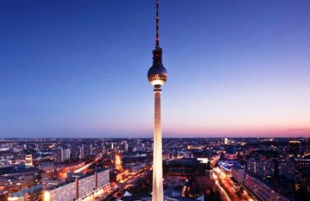 The Fernsehturm television tower with the city of Berlin in the background at sunset.