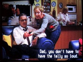 "Example of positioned lyrics: Frame from a movie showing a girl saying to her father ""Dad, you don't have to have the telly so loud"" with positioned captions"