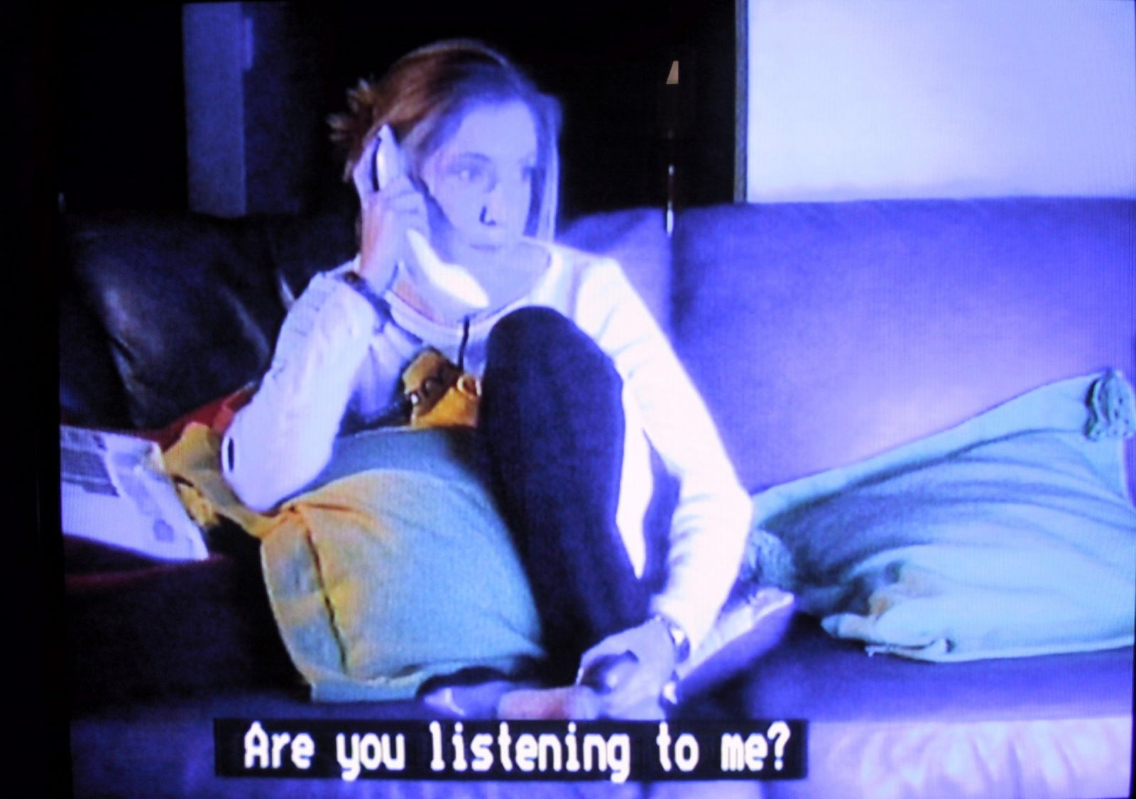 Example of a standard caption: a frame from a movie showing a girl on the phone watching a television with the caption below 'Are you listening to me?'