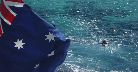 Australian flag waving in the foreground; in the background, a surfer swims in the water off the New South Wales coast