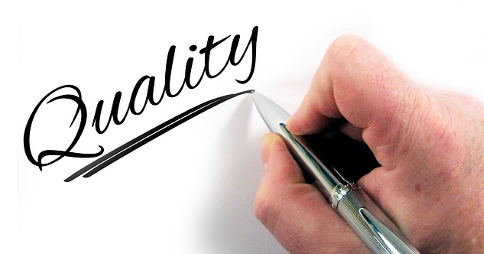 Man writing the word 'Quality' with ballpoint pen in right hand