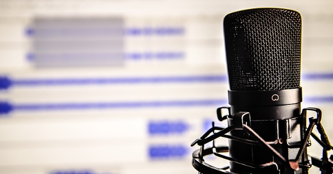 Studio microphone in front of audio waveforms on a screen in the background
