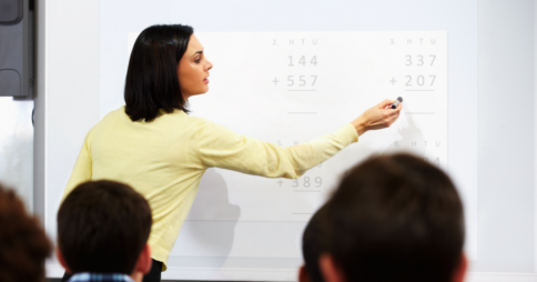 Teacher pointing at mathematics questions on a projector screen in a classroom