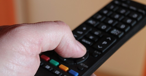 Left hand pressing 'up' button on remote control