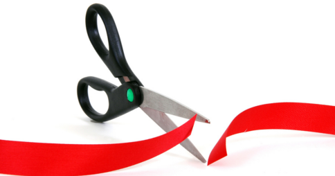 Open scissors cutting through red tape